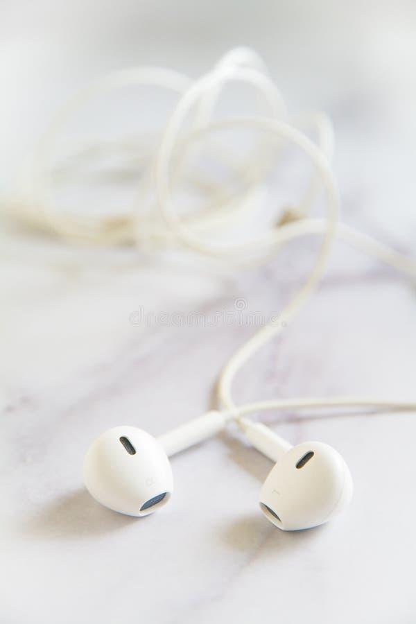 Weißer Kopfhörer und? Kabel mit unscharfem Hintergrund lizenzfreie stockfotografie
