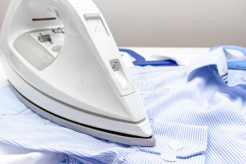 Weißer moderner elektrischer Eisenabschluß oben und blaue Hemden auf dem Tisch - Bügeln, Wäscherei und Hausarbeitkonzept lizenzfreie stockfotografie