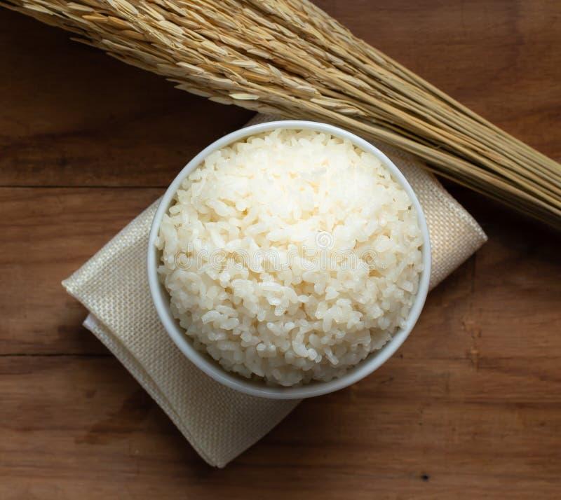 Weißer Reis des Dampfs in der weißen keramischen Schüssel auf hölzerner Tabelle für gesunde Mahlzeit stockfotos