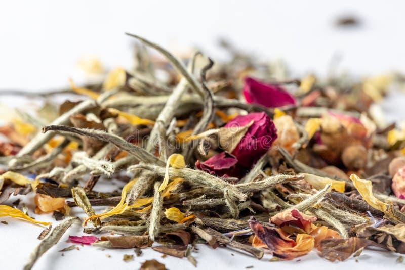 Weißer Tee mit Blumen, den Blumenblättern und den Rosebuds auf weißem Hintergrund Schließen Sie oben vom chinesischen weißen Tee  stockbild