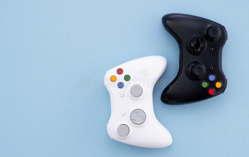 Weißer und schwarzer Steuerknüppel auf einem blauen Pastellhintergrund Gamerkonzept Prüfer für Videospiele stockfoto