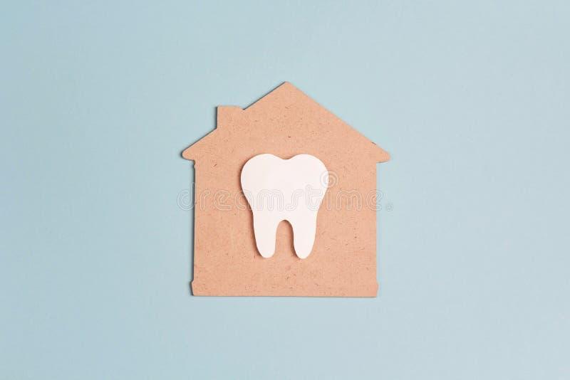 Weißer Zahn im Haussymbol auf blauem Hintergrund Zahnpflege, Zahngesundheit Flache Lage, Draufsicht, Kopienraum für Text stockbild