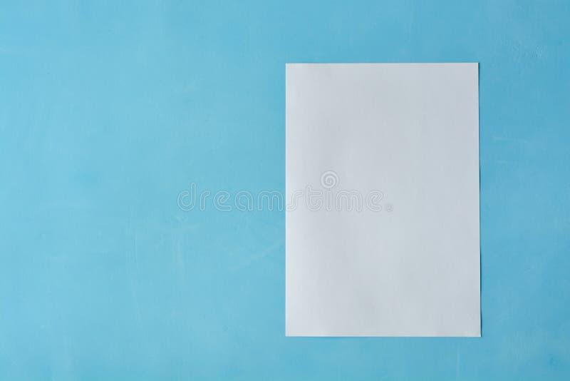 Weißes Blattpapier isoleted auf dem hellblauen Hintergrund lizenzfreie stockbilder