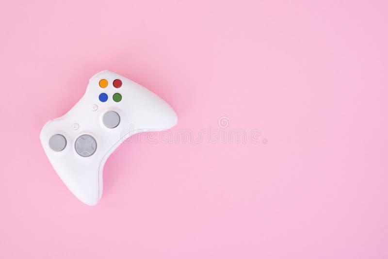 Weißes gamepad, Prüfer auf einem rosa Pastellhintergrund Weißer Steuerknüppel wird auf einem rosa Hintergrund lokalisiert stockfotos