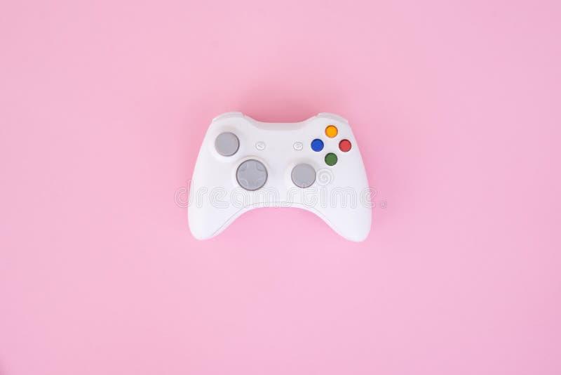 Weißes gamepad, Prüfer auf einem rosa Pastellhintergrund Weißer Steuerknüppel wird auf einem rosa Hintergrund lokalisiert lizenzfreie stockfotos
