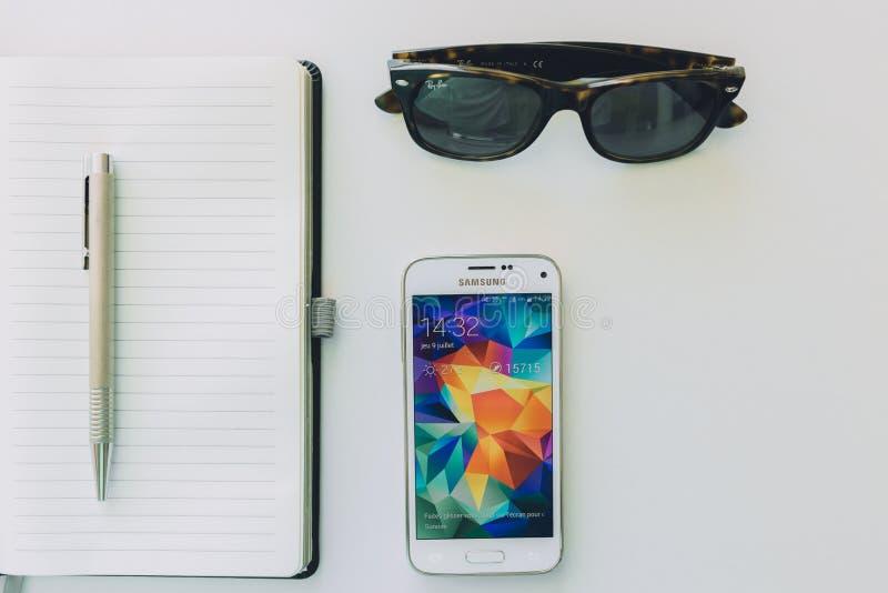 Weißes Samsung Smartphone neben Sonnenbrille, Stift und weißem Notizbuch stockfotografie