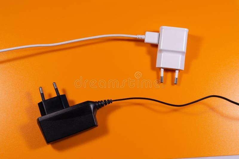 Weißes und schwarzes allgemeinhinladegerät auf orange Hintergrund lizenzfreie stockfotografie