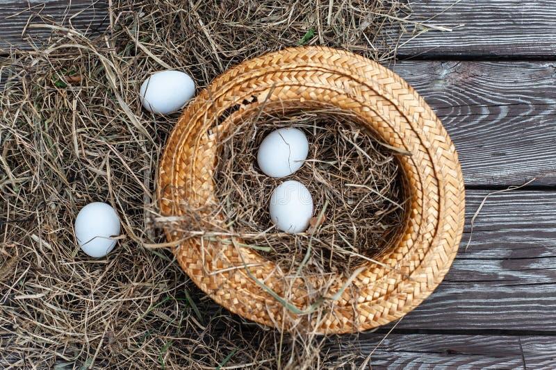 Wei?e Eier legt in den gelben Strohhut als Nest mit trockenem Heuinnere auf das h?lzerne gealterte Brett lizenzfreies stockfoto