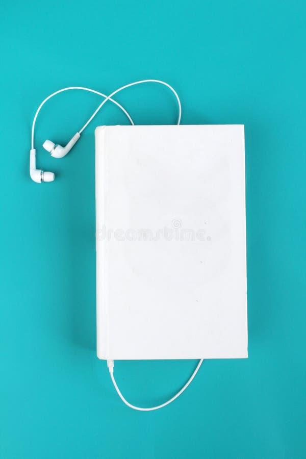Wei?e Kopfh?rer und Buch Lokalisiert auf blauem Hintergrund mit Raum f?r Text Konzept, zum auf Audiob?cher zu h?ren stockfoto