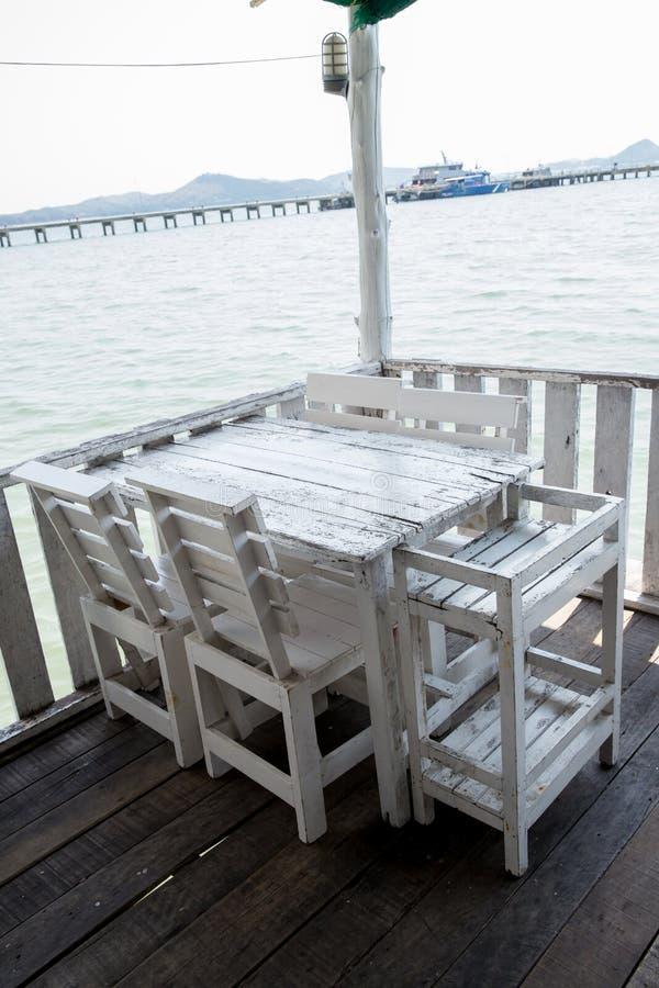 Wei?e Tabellen und St?hle im Restaurant leerer Rattanm?belkaffeesatz-Tabellenstuhl an der Bretterbodenseefront durch das Meer stockbilder