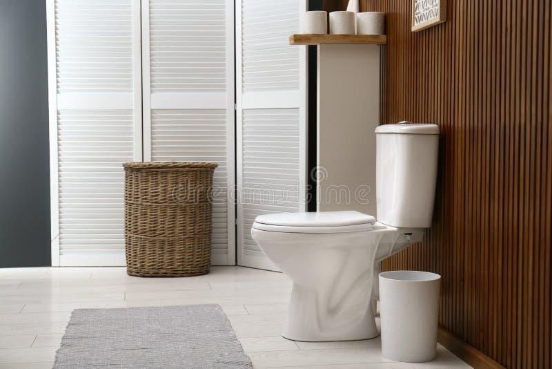 Wei?e Toilettensch?ssel nahe h?lzerner Wand im Badezimmerinnenraum stockbild