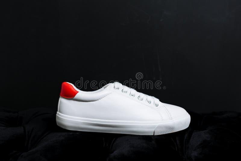 Wei?e Turnschuhe mit einer roten R?ckseite auf einem dunklen Hintergrund lizenzfreie stockfotografie
