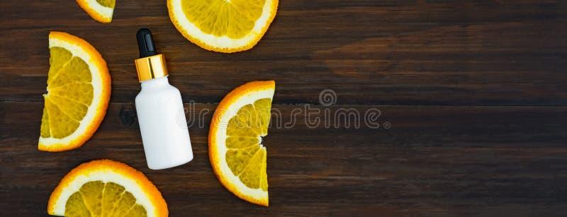 Wei?e Vitamin- Cflasche und -?l gemacht vom orange Fruchtauszug, Modell der Sch?nheitsproduktmarke Draufsicht ?ber den h?lzernen  lizenzfreies stockbild