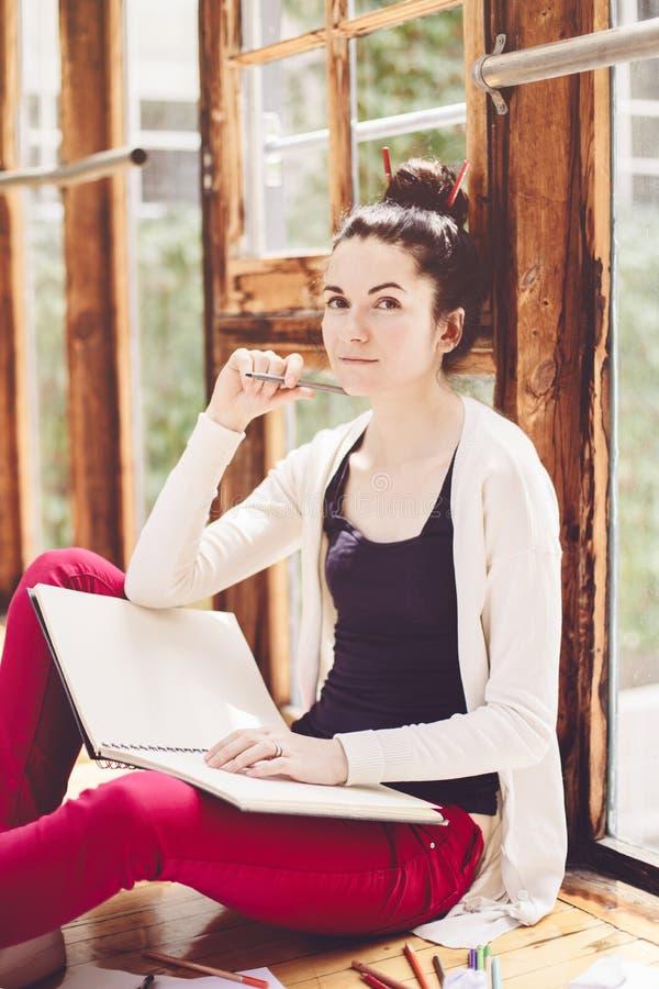 Wei?er kaukasischer junger brunette weiblicher K?nstler der Studentin, der auf Boden in der Collegeuniversit?t sitzt lizenzfreie stockfotografie