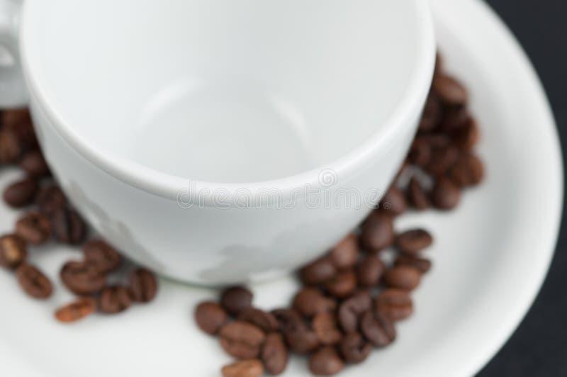 Wei?er Tasse Kaffee und Kaffeebohnen auf schwarzem Hintergrund lizenzfreie stockfotografie