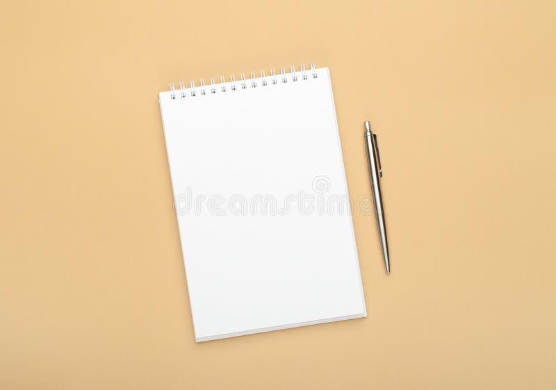Wei?es Notizbuch mit Stahlstift auf einem braunen Hintergrund B?ro, Sicherungsraum, Schein oben, Schablone, Draufsicht, flache La lizenzfreies stockbild