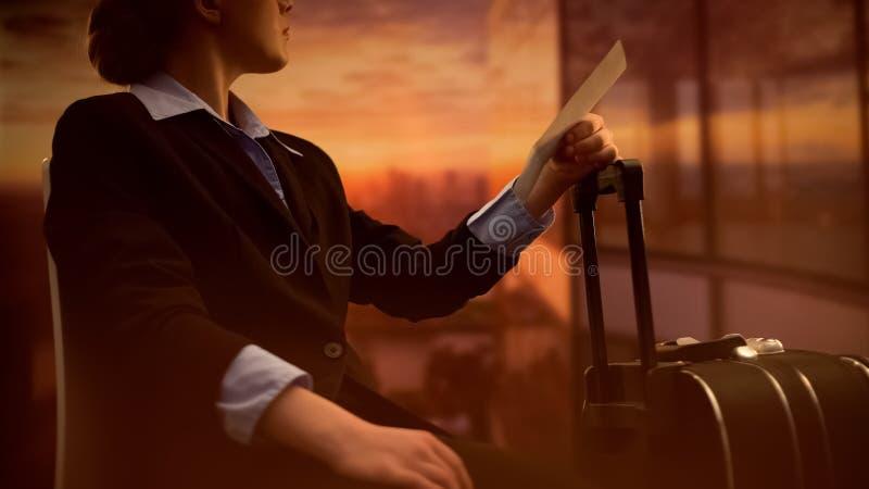 Weiblich mit Gepäckholdingkarte, Warteflug am Flughafen, träumend lizenzfreie stockbilder