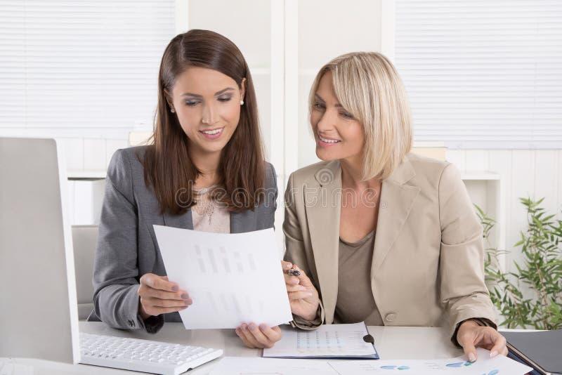 Weibliche ältere und Junior- Manager, die an Schreibtisch Arbeits-togeth sitzen stockfoto