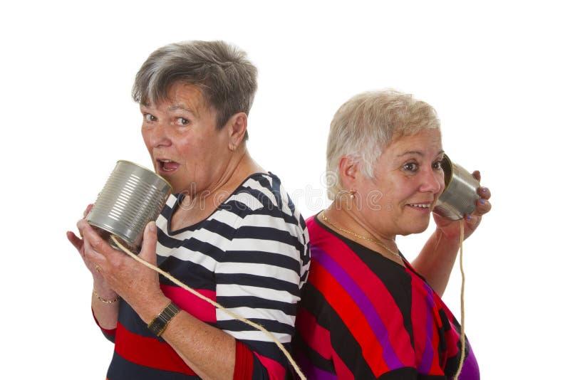 Weibliche ältere Unterhaltung mit Dosentelefon stockfotografie