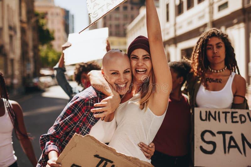 Weibliche Aktivisten, die am Protest genießen lizenzfreies stockbild