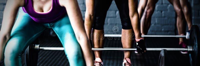 Weibliche Athleten, die Barbells anheben lizenzfreies stockfoto