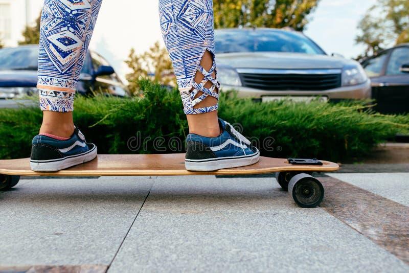 Weibliche Beine in den bunten Hosen, die auf longboard stehen Longboard-Mädchen auf der Straße lizenzfreies stockbild