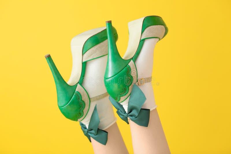 Weibliche Beine in den grünen Schuhen und den Socken des hohen Absatzes stockfoto