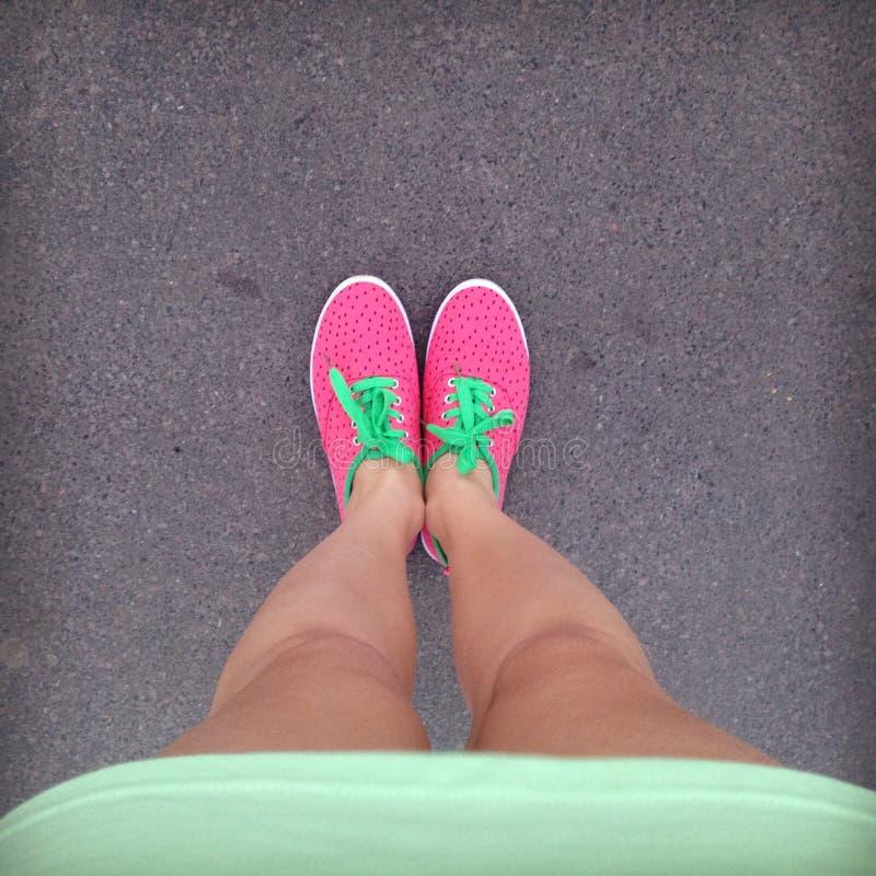 Weibliche Beine in den hellen rosa Turnschuhen mit grünen Spitzeen auf dem asph lizenzfreie stockbilder