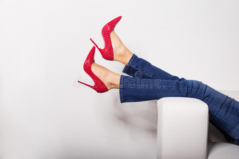 Weibliche Beine in den Jeans und in den roten hohen Absätzen stockfotografie