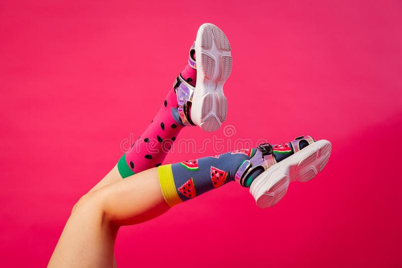 Weibliche Beine in den schwarzen Schuhen mit Fersen und hellen Farbsocken lizenzfreies stockbild