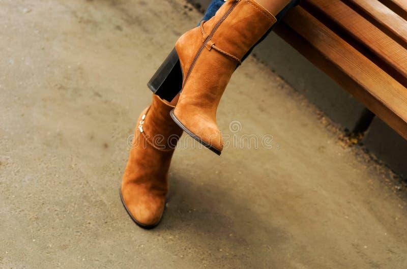 Weibliche Beine in den Stiefeln der Herbsthohen absätze in der Straße lizenzfreie stockbilder