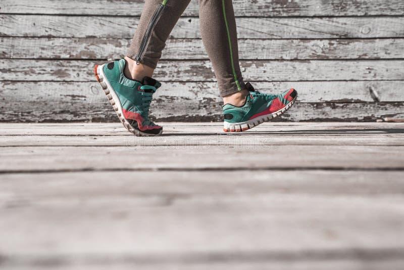 Weibliche Beine in den Turnschuhen auf einem hölzernen Hintergrund stockbild