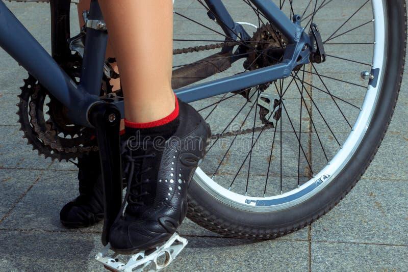 Weibliche Beine in den Turnschuhen auf Fahrrad lizenzfreie stockfotos