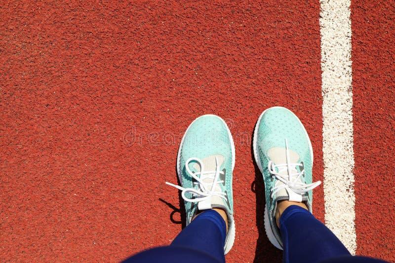 Weibliche Beine in den Turnschuhen auf rotem athletischem Bahnhintergrund stockfotografie