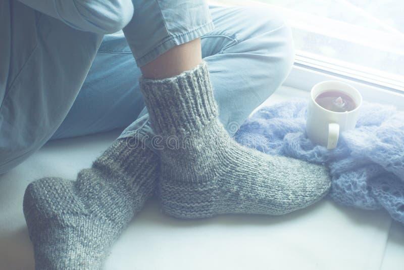 Weibliche Beine in den warmen woolen Socken und heißes Getränk auf Fensterbrett lizenzfreies stockfoto