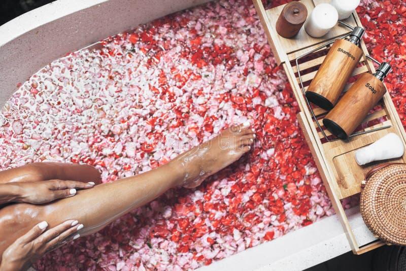 Weibliche Beine in der Badewanne mit den Blumenblumenblättern und den Schönheitsprodukten auf hölzernem Behälter lizenzfreie stockbilder