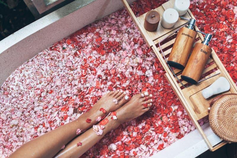 Weibliche Beine in der Badewanne mit den Blumenblumenblättern und den Schönheitsprodukten auf hölzernem Behälter stockfotos