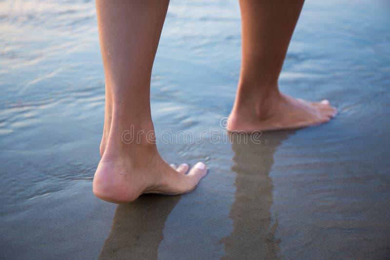 Weibliche Beine, die in Wasser auf Strand gehen stockbild
