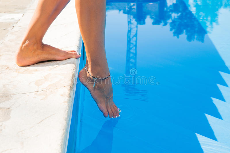 Weibliche Beine nahe schwimmen Pool stockfotos