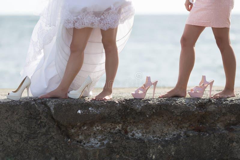Weibliche Beine und Schuhe auf Hintergrund von Meer lizenzfreie stockbilder