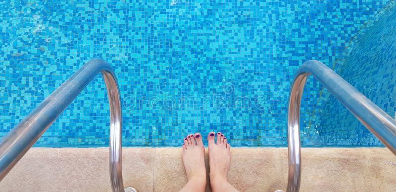 Weibliche bloße Füße, die am Rand der Swimmingpoolhälfte bereit hereinzukommen stehen stockbilder