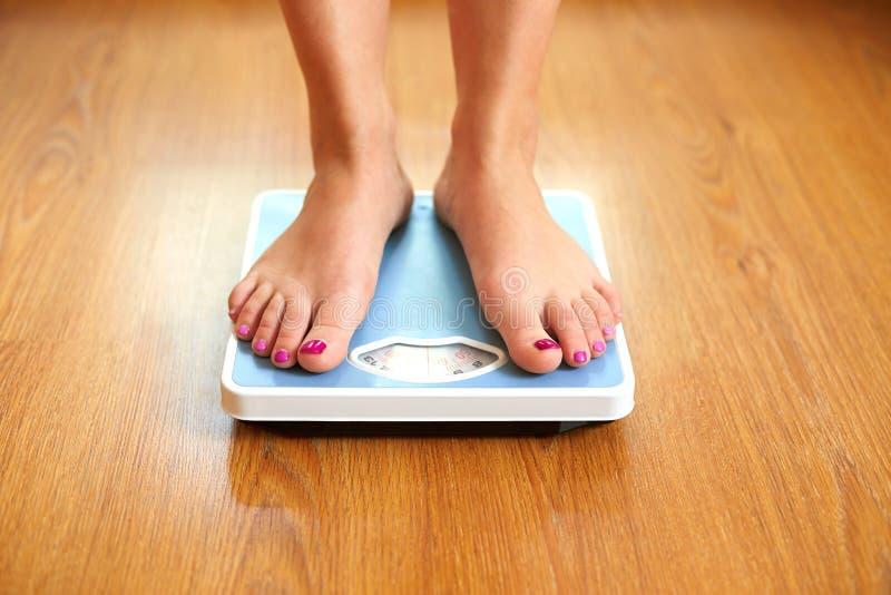 Weibliche bloße Füße mit Gewichtsskala lizenzfreie stockfotos