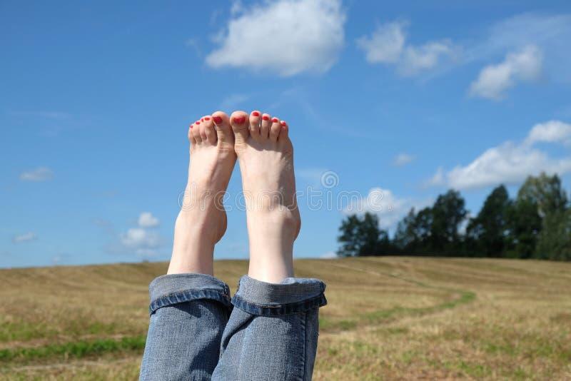 Weibliche bloße Füße mit roten Nägeln gegen Sommer gestalten Nahaufnahme landschaftlich stockbild