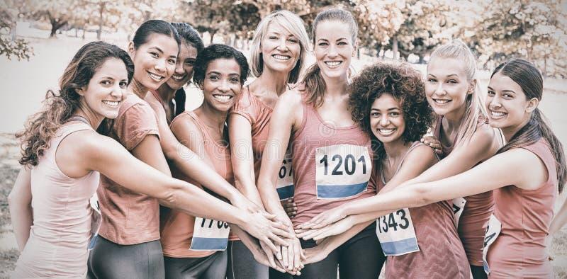 Weibliche Brustkrebs-Marathonläufer, die Hände stapeln lizenzfreie stockbilder