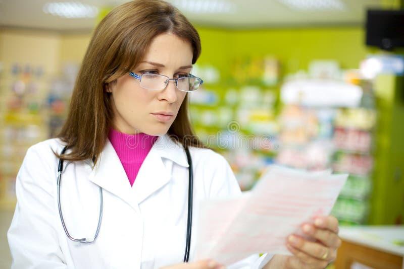 Weibliche Doktorleseverordnung in der Apotheke stockbilder