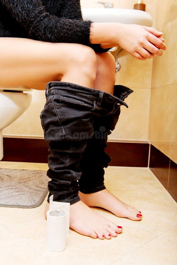 Weibliche Einstellung an einer Toilette mit ihren Hosen unten stockbild