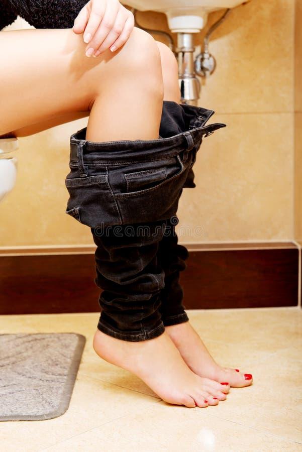 Weibliche Einstellung an einer Toilette mit ihren Hosen unten lizenzfreies stockbild