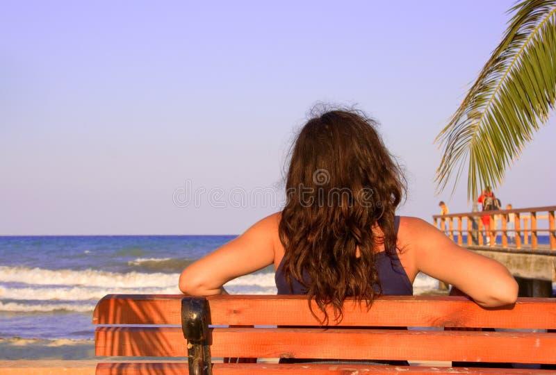 Weibliche Entspannung auf einer Strandbank lizenzfreie stockbilder