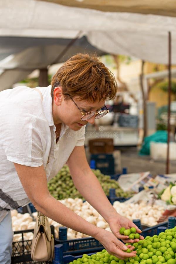 Weibliche Erntekirschpflaumen am Lebensmittelgesch?ftmarkt lizenzfreie stockbilder
