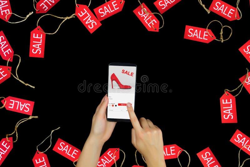 Weibliche erwachsene Hände der Frau mit dem Smartphone, der neue rote hohe Absätze der Mode mit Verkauf oder Rabatt wählt und her stockfotos